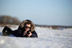 As mentiras da pessoa na neve e no gelo surgem fotografias Ajardine o fotógrafo em um revestimento com colar da pele Imagens de Stock Royalty Free