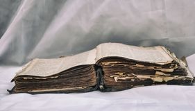 As mentiras desalinhado antigas velhas do ` da Bíblia do ` do livro abrem na tabela com cortina branca O conceito dos ensinos de  fotografia de stock