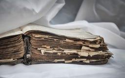 As mentiras desalinhado antigas velhas do ` da Bíblia do ` do livro abrem na tabela com cortina branca O conceito dos ensinos de  imagens de stock
