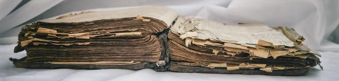 As mentiras desalinhado antigas velhas do ` da Bíblia do ` do livro abrem na tabela com cortina branca O conceito dos ensinos de  fotos de stock royalty free