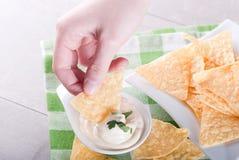 As microplaquetas de batata em uma mão mergulharam no molho Imagens de Stock Royalty Free