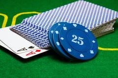 As microplaquetas de pôquer encontram-se em uma plataforma de cartões Fotografia de Stock Royalty Free