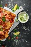 as microplaquetas dos nachos da tortilha do Maxican-estilo cobertas com salsa do tomate, os pimentões cortados e queijo derretido Fotografia de Stock