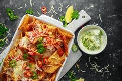 as microplaquetas dos nachos da tortilha do Maxican-estilo cobertas com salsa do tomate, os pimentões cortados e queijo derretido Fotos de Stock
