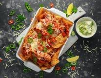 as microplaquetas dos nachos da tortilha do Maxican-estilo cobertas com salsa do tomate, os pimentões cortados e queijo derretido Imagem de Stock