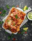 as microplaquetas dos nachos da tortilha do Maxican-estilo cobertas com salsa do tomate, os pimentões cortados e queijo derretido Imagem de Stock Royalty Free