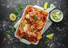 as microplaquetas dos nachos da tortilha do Maxican-estilo cobertas com salsa do tomate, os pimentões cortados e queijo derretido Foto de Stock Royalty Free