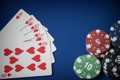 As microplaquetas e a mão de pôquer de jogo do resplendor real no azul sentiram o fundo Fotografia de Stock
