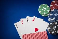 As microplaquetas e o cartão de jogo do pôquer no azul sentiram o fundo Fotos de Stock