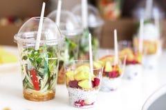 As mini sobremesas e o vegetal saudável microgreen saladas em canaps dos copos do plástico Tabela servida de abastecimento Fotografia de Stock