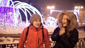 As moças andam no inverno no quadrado central da cidade perto da árvore de Natal Feriado, neve, alegria video estoque