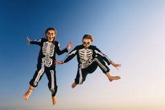 As moças em trajes de Dia das Bruxas saltam altamente com divertimento foto de stock