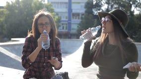 As moças estão sentando-se no parque na queda e na água potável Passeio, amizade, uma comunicação video estoque