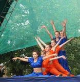 As moças no terno brilhante dançam e mostram conluios acrobáticos no sc Fotografia de Stock Royalty Free
