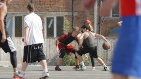 As moças olham para os homens novos que jogam o streetball no ar livre (o movimento lento) video estoque