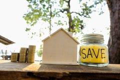 As moedas colocadas no assoalho de madeira, salvar o dinheiro para preparam-se no futuro e abrigam-se foto de stock