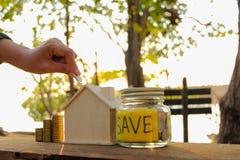 As moedas colocadas no assoalho de madeira, salvar o dinheiro para preparam-se no futuro e abrigam-se imagens de stock