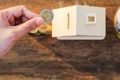 As moedas colocadas no assoalho de madeira, salvar o dinheiro para preparam-se no futuro e abrigam-se imagens de stock royalty free