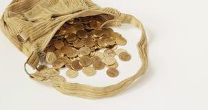 As moedas de ouro da pilha transbordam do lapso de tempo marrom velho do saco video estoque