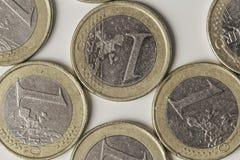 As moedas de um Euro fecham-se acima em um fundo branco Fotografia de Stock