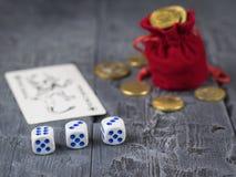 As moedas derramaram de um saco e de um dado vermelho em uma tabela escura de madeira fotografia de stock royalty free