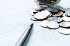 As moedas dispersaram do frasco de vidro, a caderneta bancária da pena e de conta poupança ou balanço financeiro na tabela da mes Fotos de Stock
