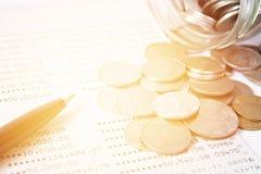As moedas dispersaram do frasco de vidro, a caderneta bancária da pena e de conta poupança ou balanço financeiro na tabela da mes Foto de Stock