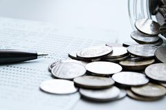 As moedas dispersaram do frasco de vidro, a caderneta bancária da pena e de conta poupança ou balanço financeiro na tabela da mes Imagem de Stock Royalty Free