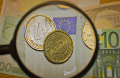 As moedas e as cédulas aumentaram a lente de aumento Fotografia de Stock