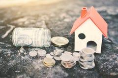 As moedas e a casa de madeira no conceito do fundo da rocha salvar o dinheiro para a casa imagens de stock royalty free