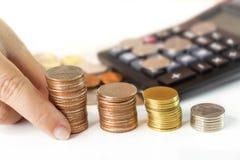 As moedas empilham com a calculadora na tabela branca Fotografia de Stock
