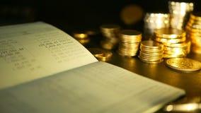 As moedas empilham e a caderneta bancária da conta bancária de economia conceitos para a hipoteca e os organismos de investimento vídeos de arquivo