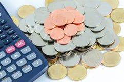 As moedas empilham e calculadora isolada sobre o fundo branco Fotos de Stock Royalty Free