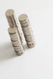 As moedas empilham isolado no branco Fotos de Stock