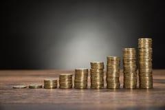 As moedas empilham na tabela Fotos de Stock