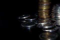 As moedas empilham no fundo preto na parede do conceito e no dinheiro forte imagens de stock royalty free