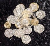As moedas na água espirram em um fundo preto Foto de Stock