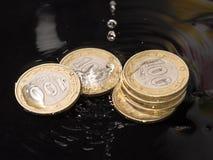 As moedas na água espirram em um fundo preto Imagens de Stock