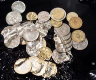 As moedas na água espirram em um fundo preto Fotografia de Stock