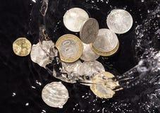 As moedas na água espirram em um fundo preto Imagem de Stock