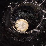 As moedas na água espirram em um fundo preto Fotos de Stock Royalty Free