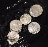 As moedas na água espirram em um fundo preto Imagens de Stock Royalty Free