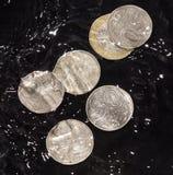 As moedas na água espirram em um fundo preto Fotografia de Stock Royalty Free