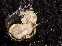 As moedas na água espirram em um fundo preto Fotos de Stock
