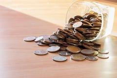 As moedas no dinheiro rangem com luz do por do sol no dinheiro da economia Foto de Stock