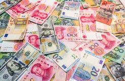 As moedas principais do mundo como o fundo do dinheiro fotografia de stock