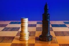 As moedas são formadas como um rei em um tabuleiro de xadrez imagem de stock