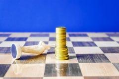 As moedas são formadas como um rei em um tabuleiro de xadrez Foto de Stock