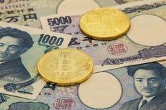 As moedas simbólicas do bitcoin na pilha de muitos datilografam cédulas de japão imagens de stock royalty free