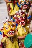 As monges com cilindros executam uma dança mascarada e trajada religiosa do mistério do budismo tibetano foto de stock